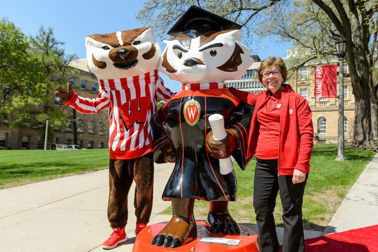 Chancellor Blank standing with Bucky the badger next to the Bucky statue dressed in a cap and gown for graduation.