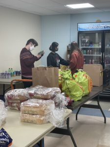 volunteers place food inside bags at a local for pantry.