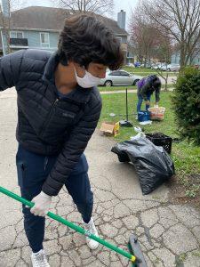 Hub intern Diego sweeps glass off the driveway.