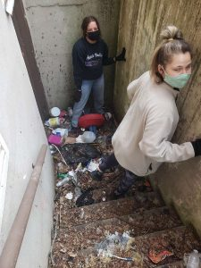 Volunteers clean up trash in the backyard of a property under Porchlight care.